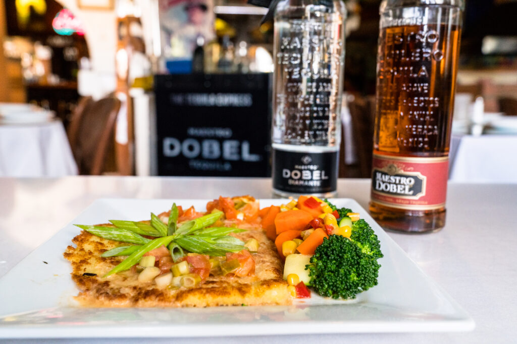 Salmon Mandarin with vegetables and bottles of tequila Dobel in the background