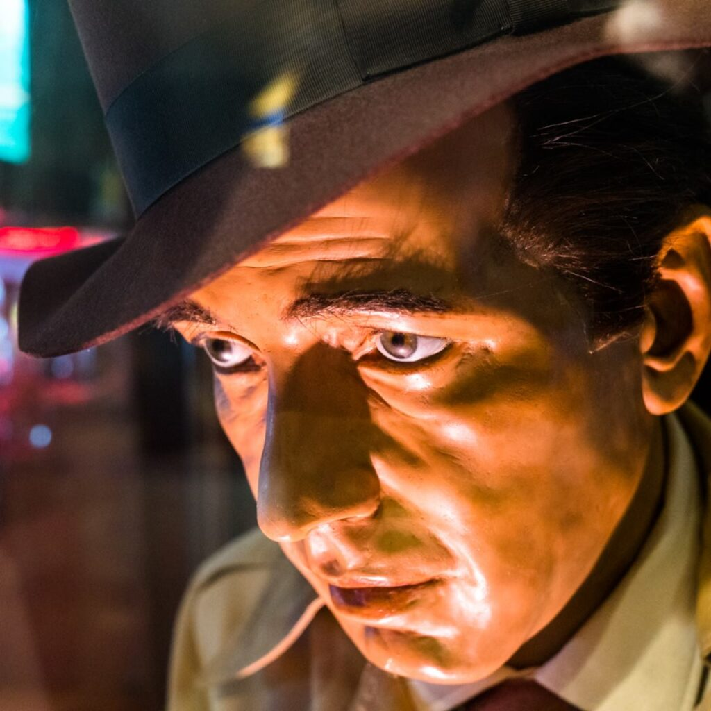 A close up of the face of a life-size Humphrey Bogart statue wearing a hat.