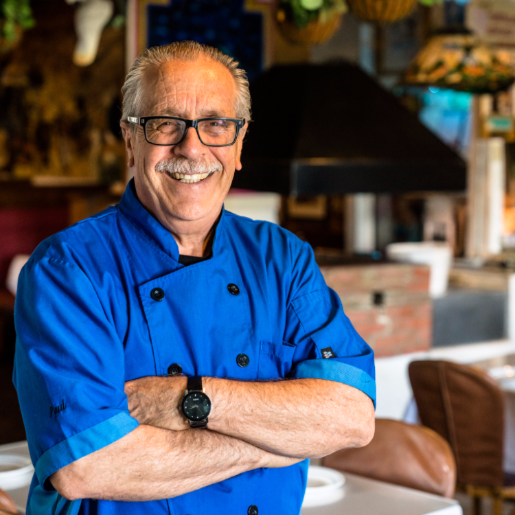 Carlos Haro, the owner, in a blue shirt with his arms crossed in the middle of the restaurant