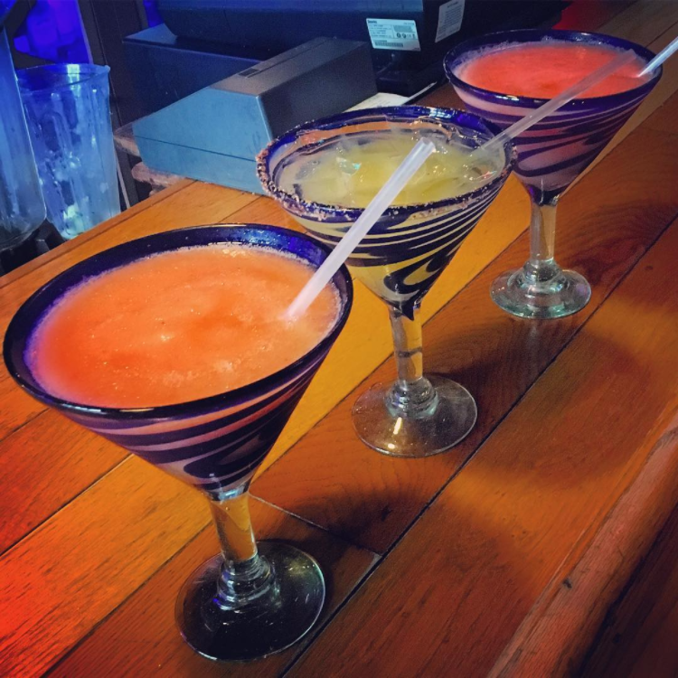 three margaritas of different flavors with straws on a bar