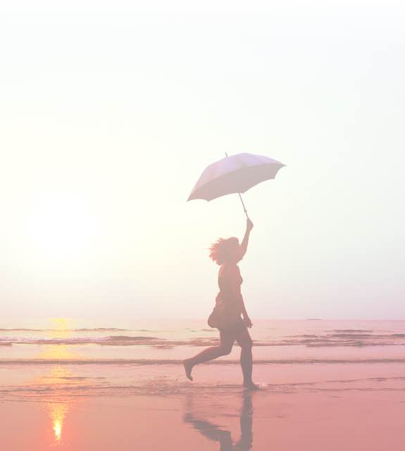 Girl holds umbrella over head on beach