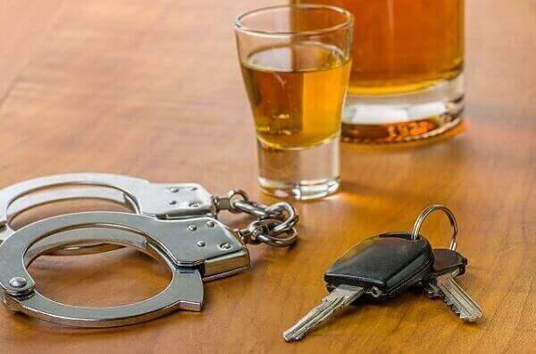 dwi - handcuffs, car keys, and shot glass