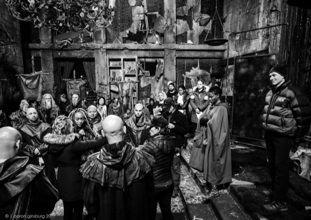 a black and white photo of the cast of The 100 at work