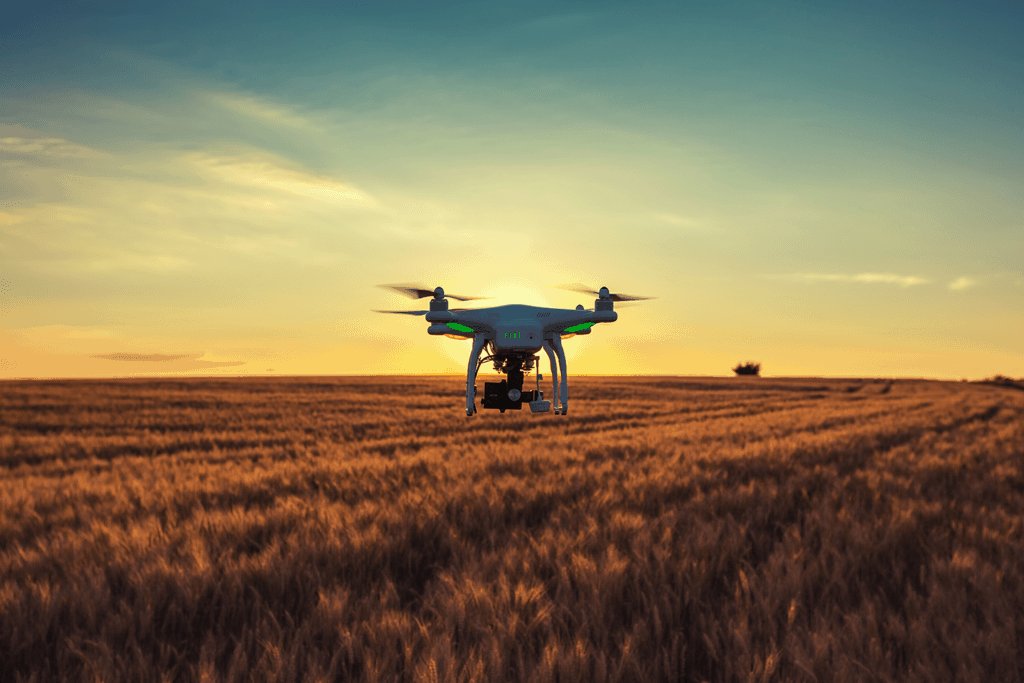 A drone hovering over a farmers field in the early morning