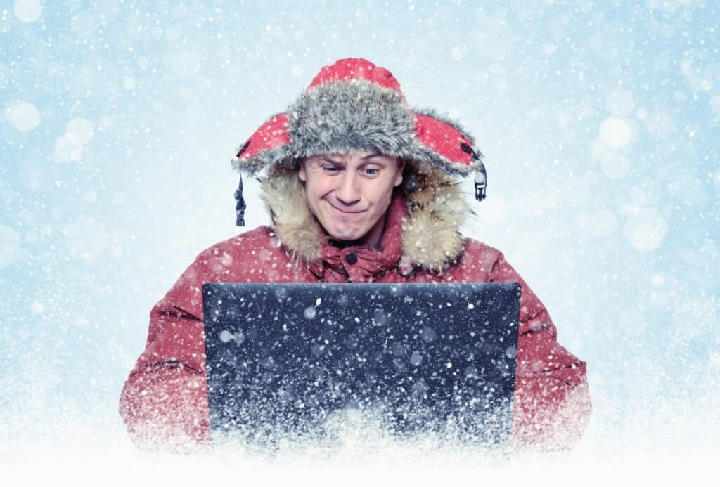 Man looking questionably at his laptop while it snows