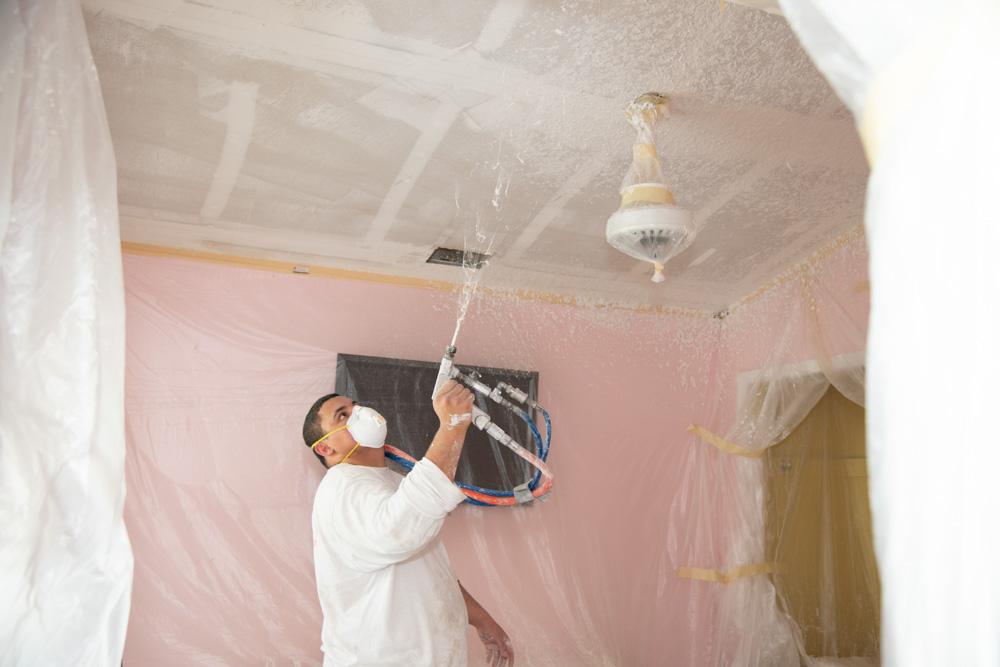 Employee Spraying Ceiling Finish