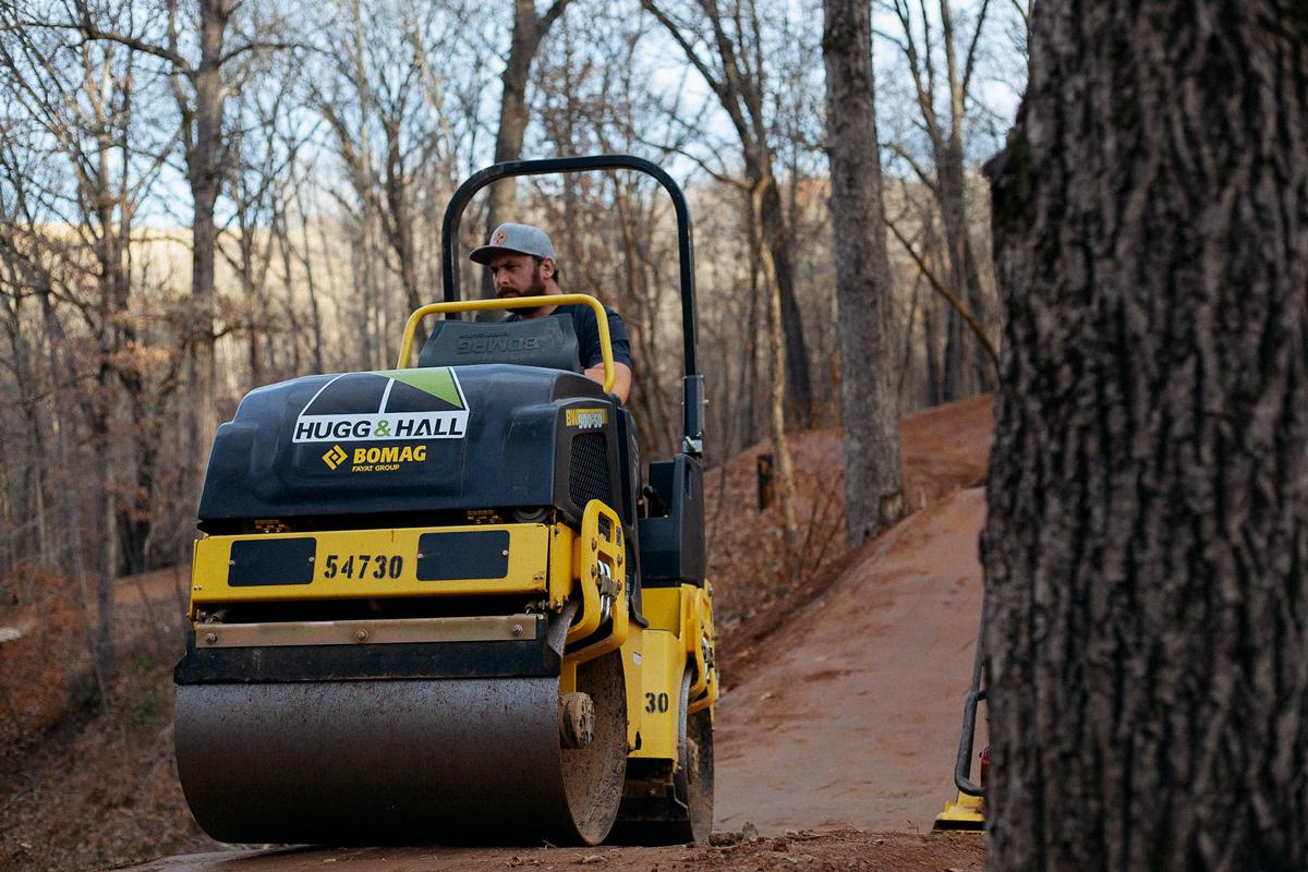 Progressive Trail Design crew member uses steamroller to pack dirt.