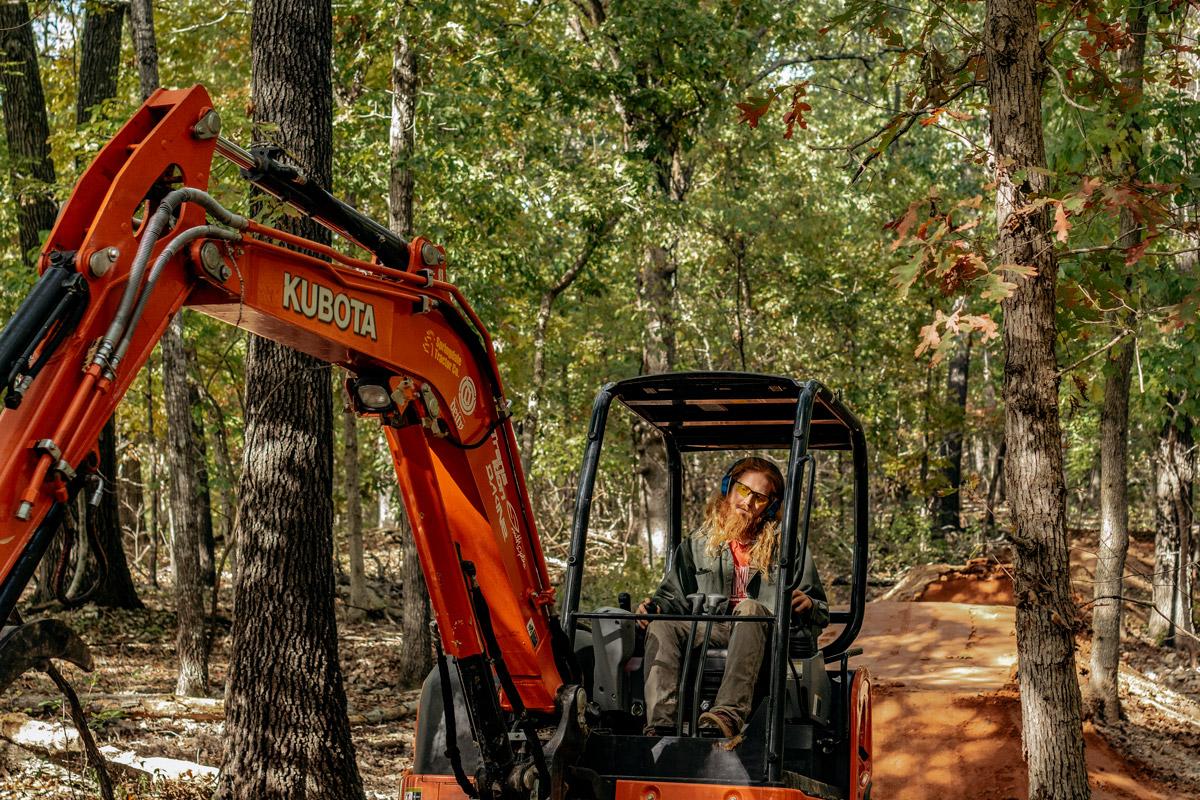 Progressive Trail Design crew member uses excavator to build trail