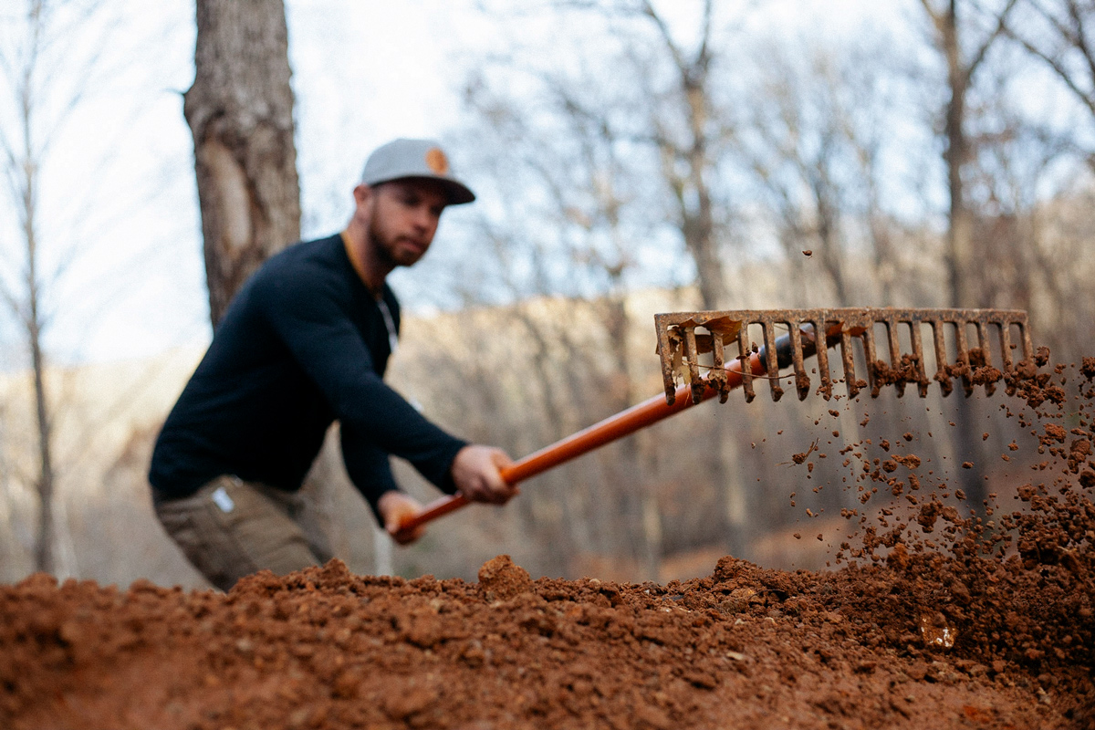 Trail builder rakes trail in Dig Clothing Company hat