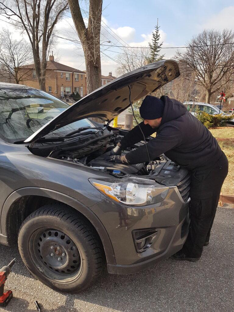 A Toronto Mobile Mechanic fixing the hood of a car