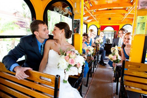 Bride and Groom inside Victorian Trolley with wood seats and full wedding party of 14 people in a 23 passenger rental leaving church heading to cescaphe ballroom Philadelphia for reception