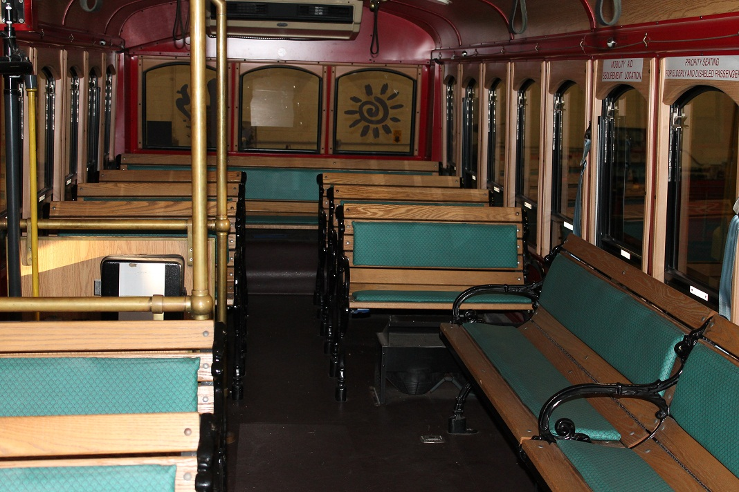 Chance Trolley rental in Philadelphia PA showing wood seats on a 27 passenger vehicle layout for bridesmaids and groomsmen with bride and groom at center of attention