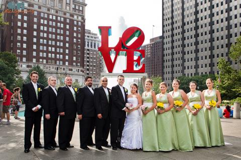 Wedding Party Love Park for photos before church on white trolley rental black tuxedo green dress yellow flowers 12 people for 23 passenger Victorian trolley in Philadelphia