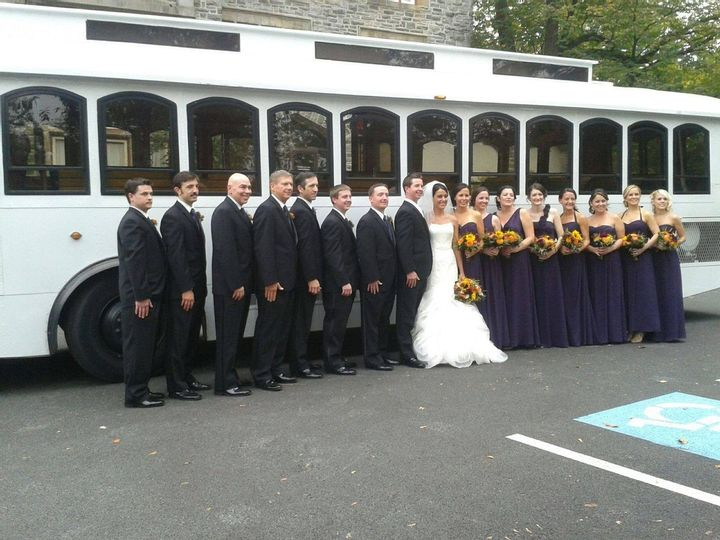 White Trolley Rental Philadelphia Wedding Party Bridemaids Grooms Men Best Man Bride Groom Red Yellow Orange Flowers outside Transportation heading to delaware from church to Cescaphe