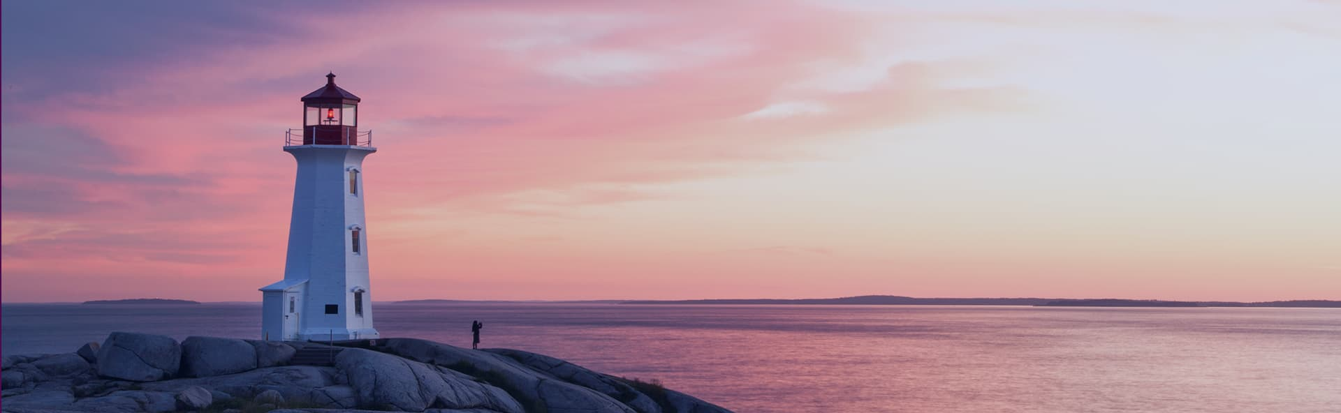 person on rock in distance with sunset