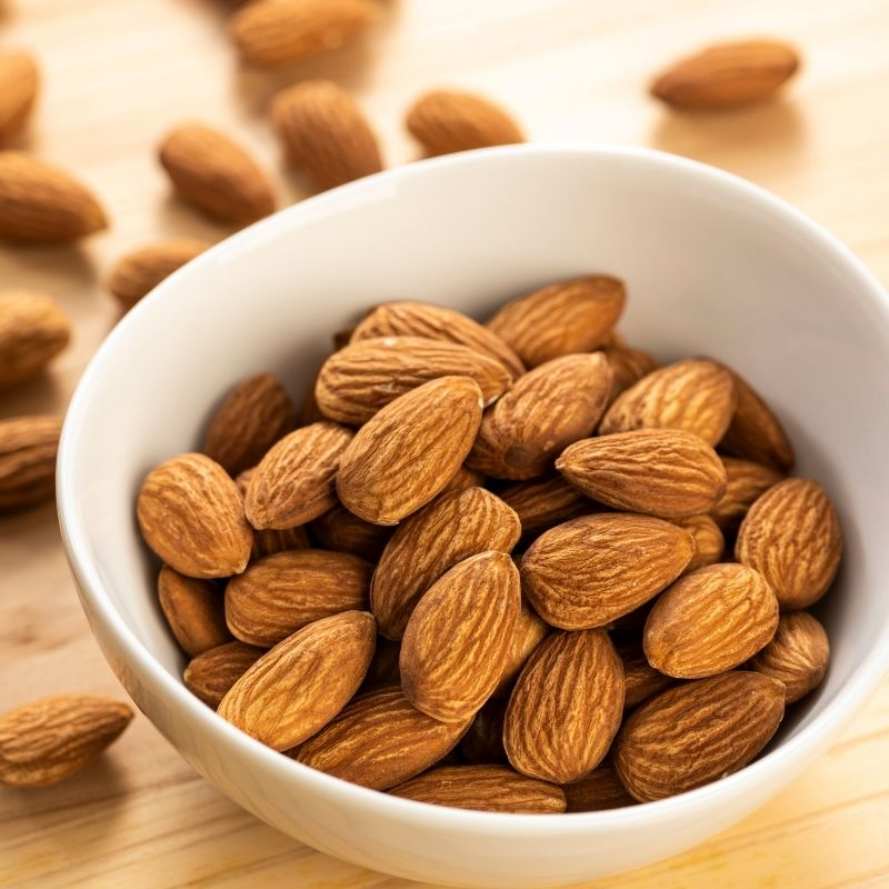 A bowl of almonds in a porcelain bowl.