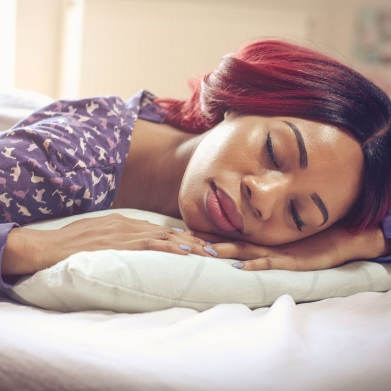A person resting on a bed.