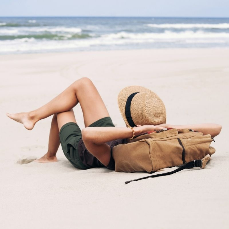 A person relaxing at the beach with a sunhat.