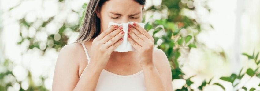 young woman covering her nose using tissue at the garden