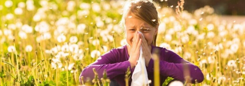 Young girl sitting at the farm while covering her nose