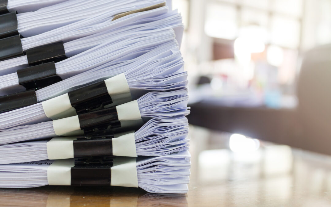 large stack of documents sitting on a desk