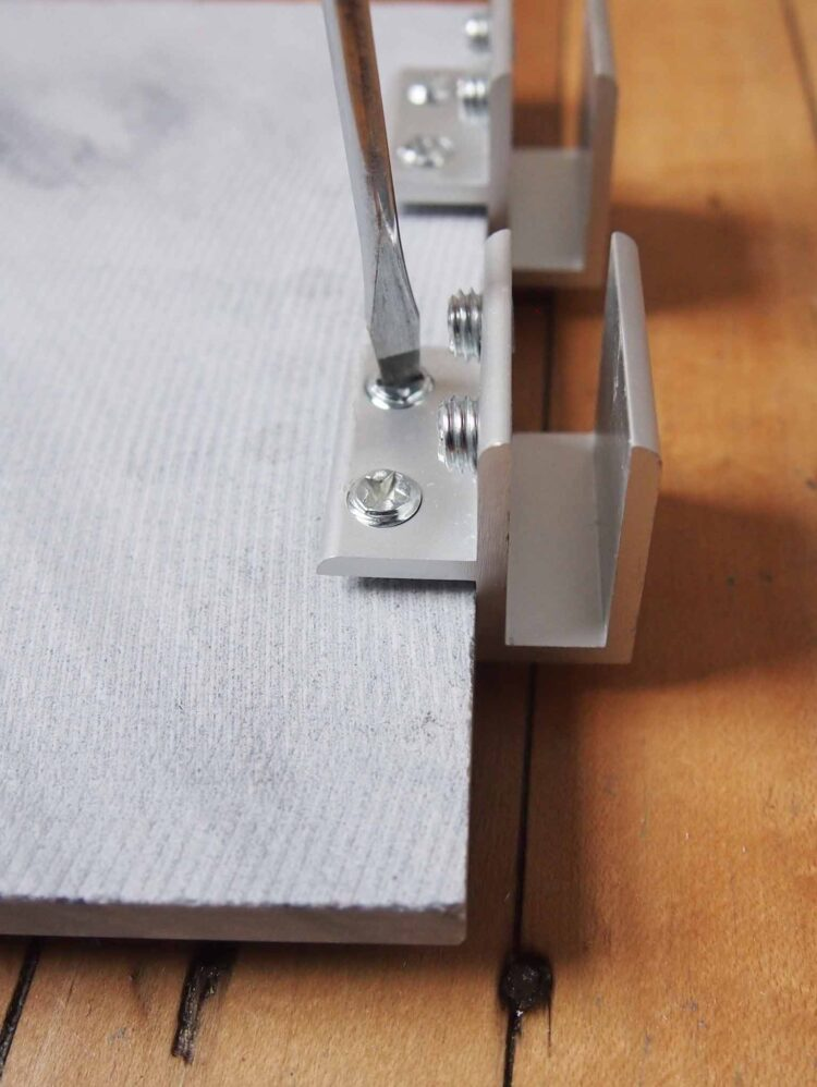 3   Arrange two brackets on one end of each long tile so that the small part of the bracket is holding the tile.