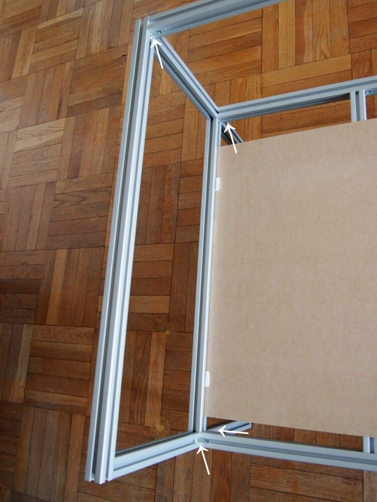 14   Attach your assemblage from step 12 to the frame you have assembled so far. Slide the MDF board into the channel and tighten the small brackets (see arrows). Make sure everything lines up nicely.