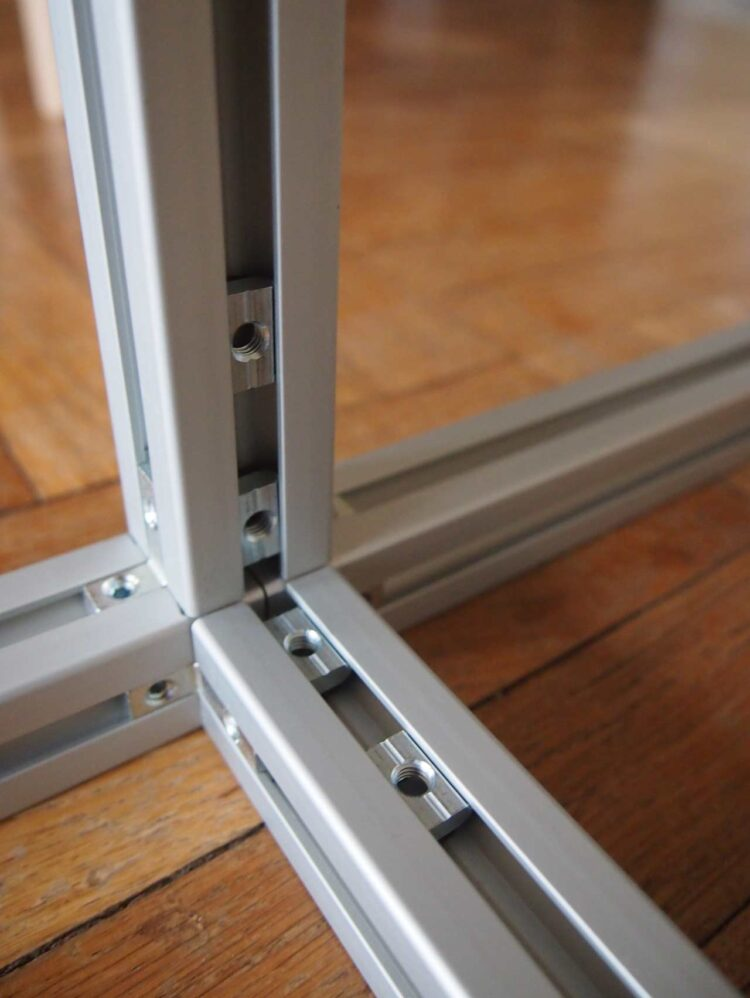 4   Then arrange all 4 nuts in the channels of the frame so that they line up with the holes in the large bracket.
