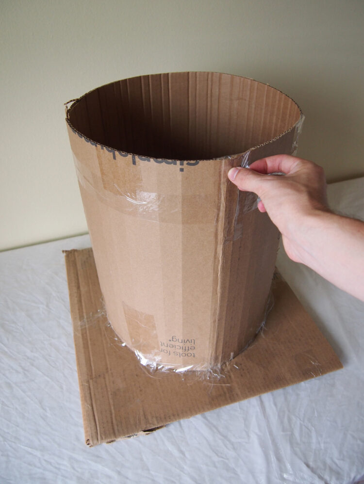 2   Tape the cardboard together, forming a cylinder. Also tape the cylinder to a wooden board (or anything sturdy you don't mind getting messy).