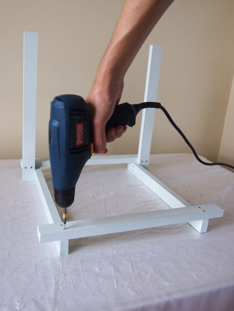 10   Secure a sixth piece at the ends of the two parallel horizontal pieces. It should hang over each horizontal piece by 1 full width of wood.