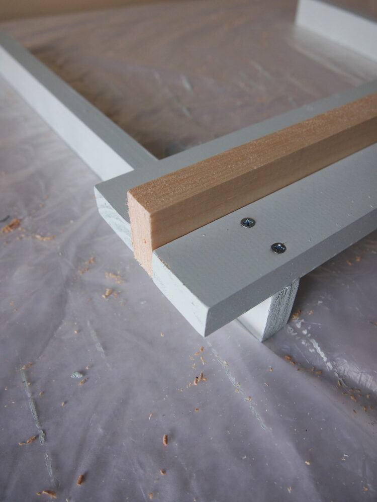 23   Using the narrow side of a spare piece of wood as a spacer, place another horizontal piece across the narrow edges of the lower pieces.