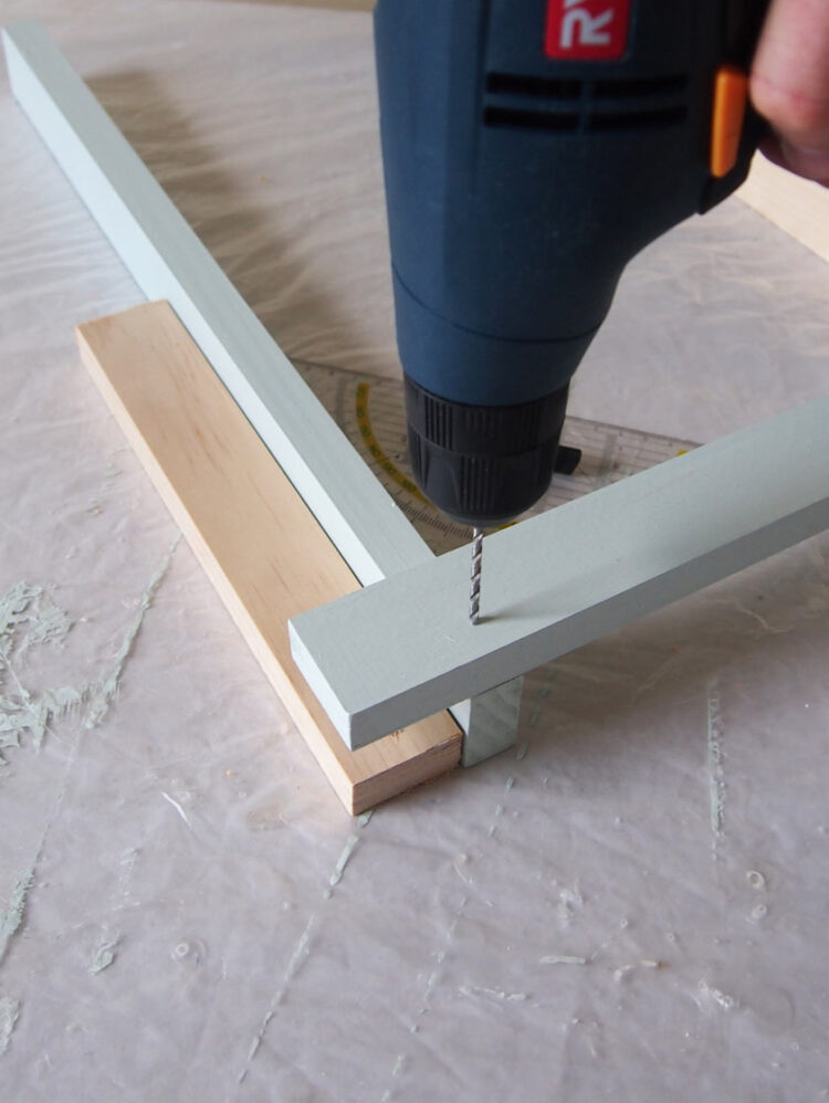 5   Use the square to confirm a 90 degree angle, hold the two pieces down, and drill two vertical holes beside each other.