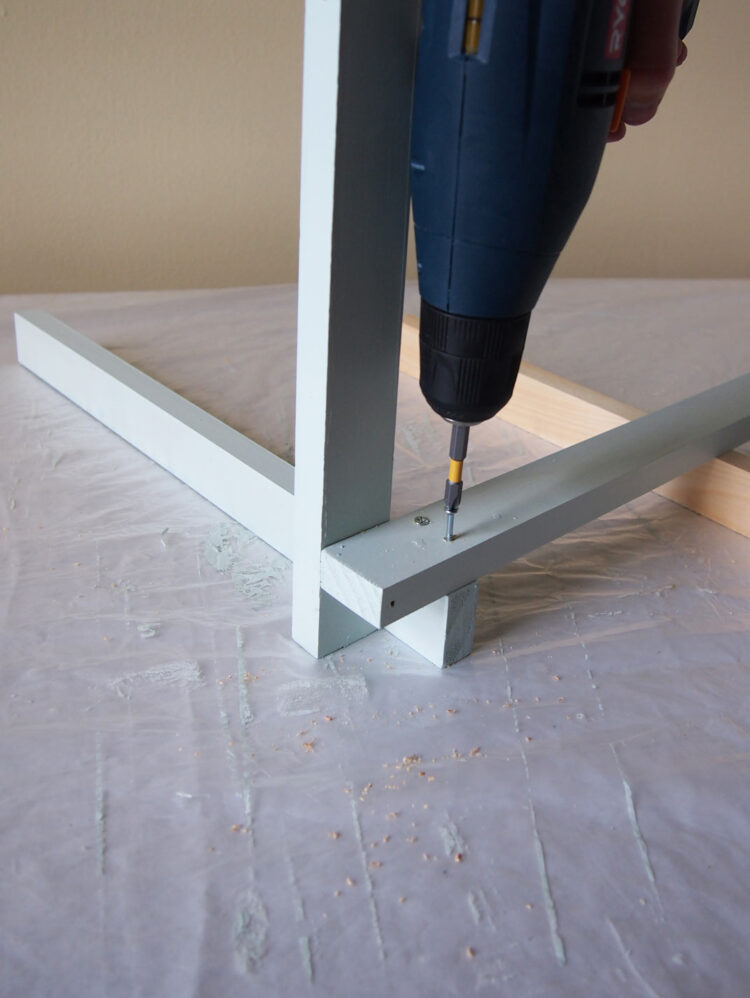 7   Position the lower piece to be vertical. Place a third piece on top of the horizontal piece, and aligned with the edge of the vertical piece. Drill and screw the pieces together.