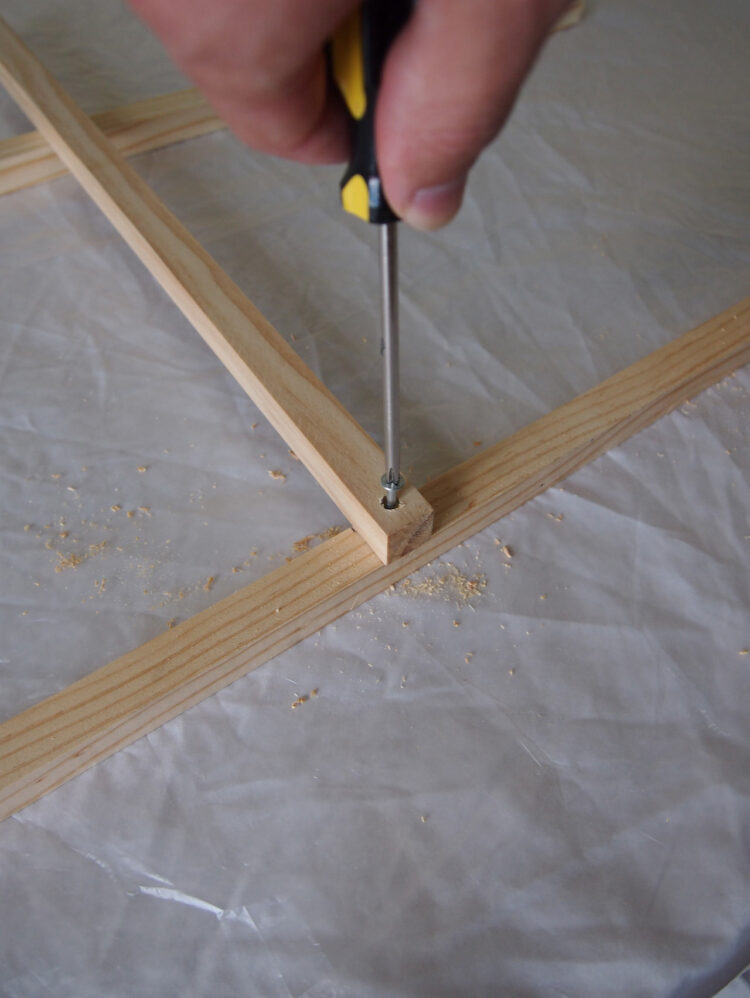 4   Twist a screw into the holes to join the two horizontal pieces to the vertical one.