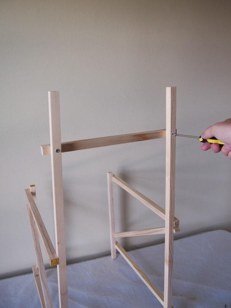 7   Leaving 1 width of wood space on either side of the frame, position a 15in (380mm) long piece 4.5in (116mm) from the top of the frame. Secure in place by drilling two holes and adding two screws.