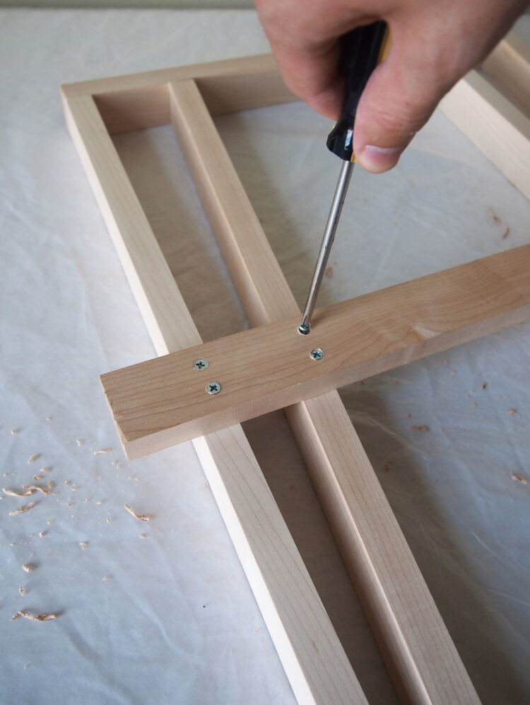 14   Hold the wood in place, drill holes and add two screws to secure the new 27.5in (70cm) piece.