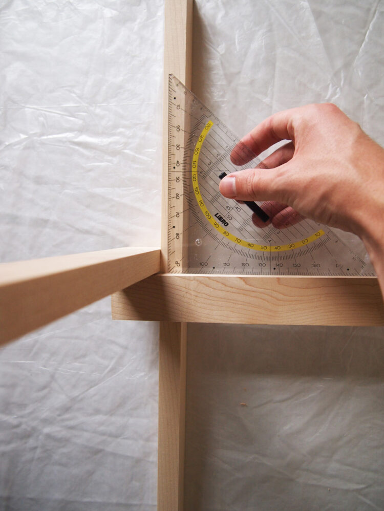 4   On the left side, align the horizontal piece 10in (25.5cm) from the top of the vertical piece. Using a spare length of wood, make sure the horizontal piece extends a full width of wood beyond the vertical piece. Use a square tool to confirm 90 degree angle.