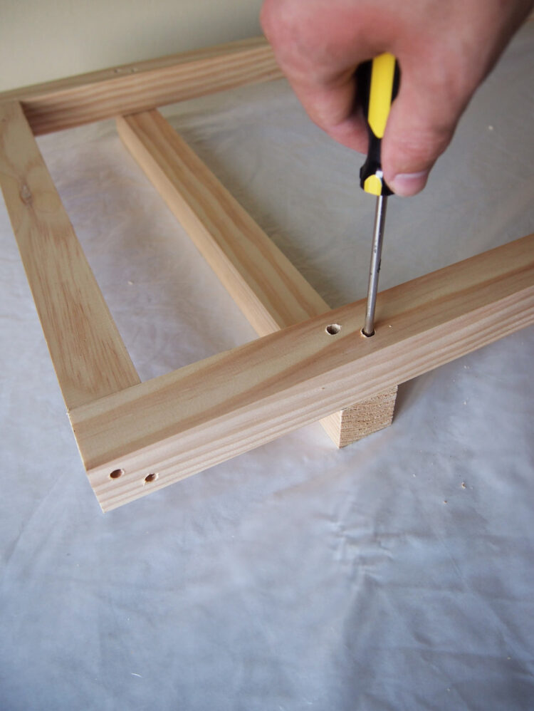 20   Drill 2 holes, countersink, and add 2 screws on each end to secure the 19in (48cm) long piece 4.5in (12cm) from the top of the top of the piece in step 18.