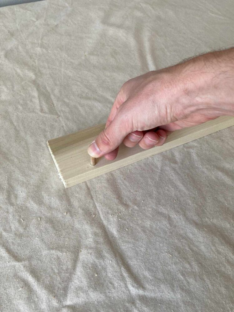 6   Add glue to the hole, and insert a dowel pin as far in as possible. Wipe away excess glue.