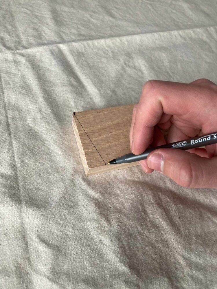 2   Mark 1/2in (1.5cm) from the end of the 106in (270cm) long piece of wood. Draw a line from that mark to the opposite edge, as photographed.