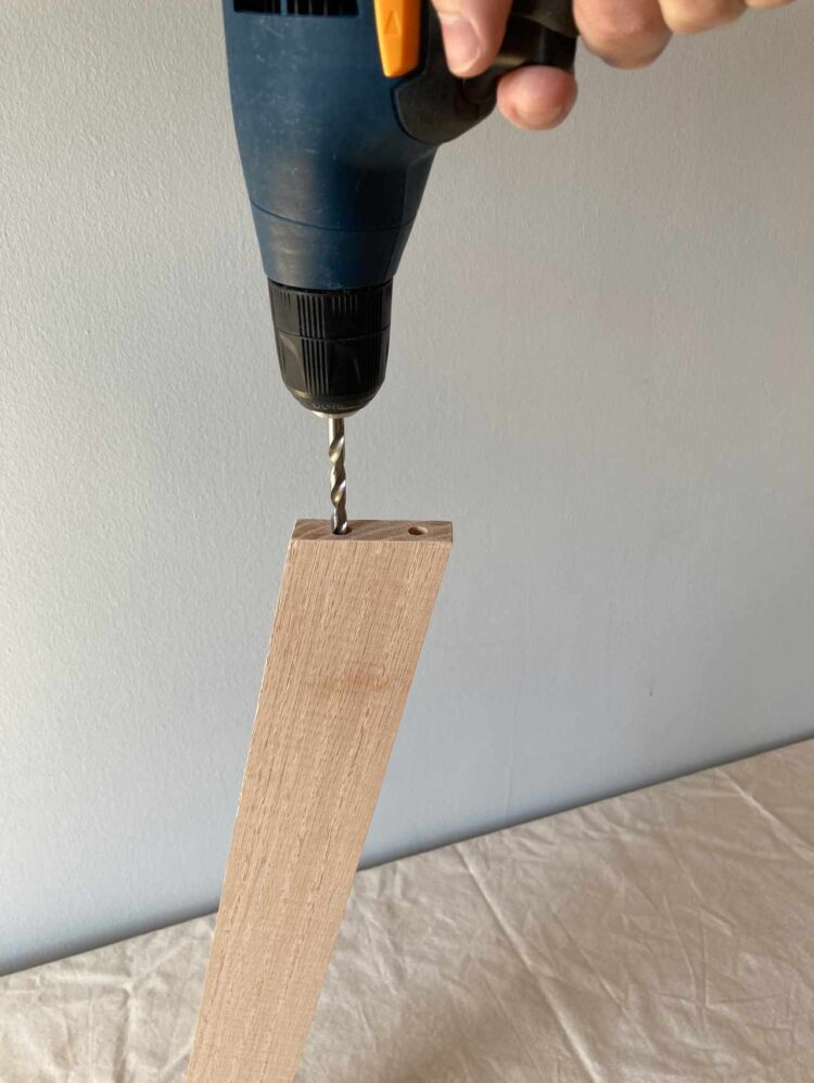 6   In one end of a piece from step 5, drill 2 pilot holes perpendicular to the angle of the wood edge. Drill larger holes inside of your pilot holes with a 1/4in drill bit.