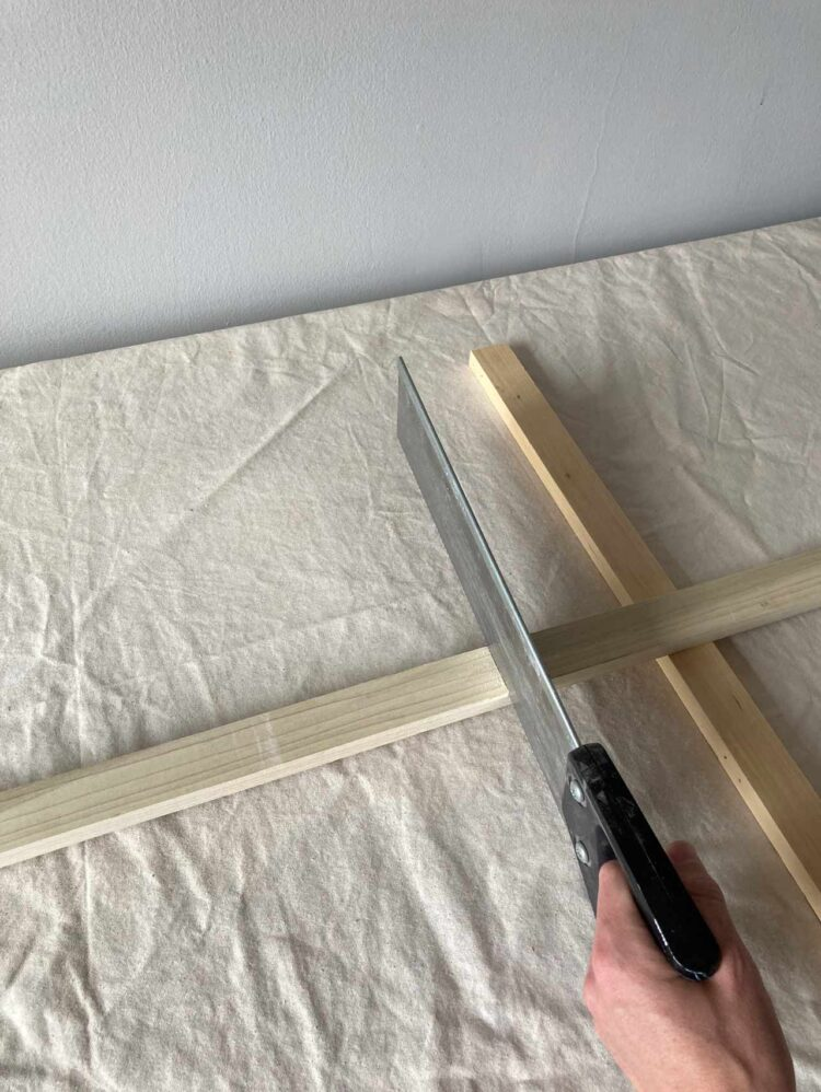 1   Propping up one side on a piece of wood, saw lengths of wood for the following steps.