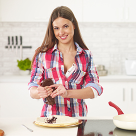 Image of woman in a kitchen pouring chocolate syrup on Tortilla