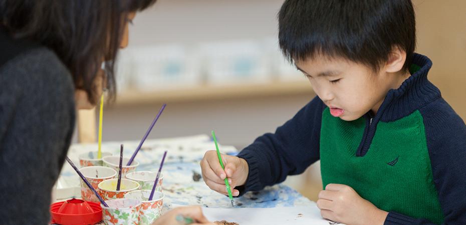 An Asian boy painting