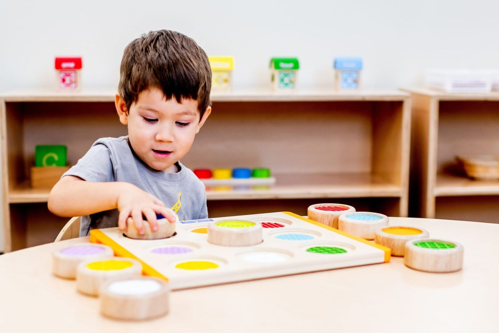 A little boy playing with wooden blocks