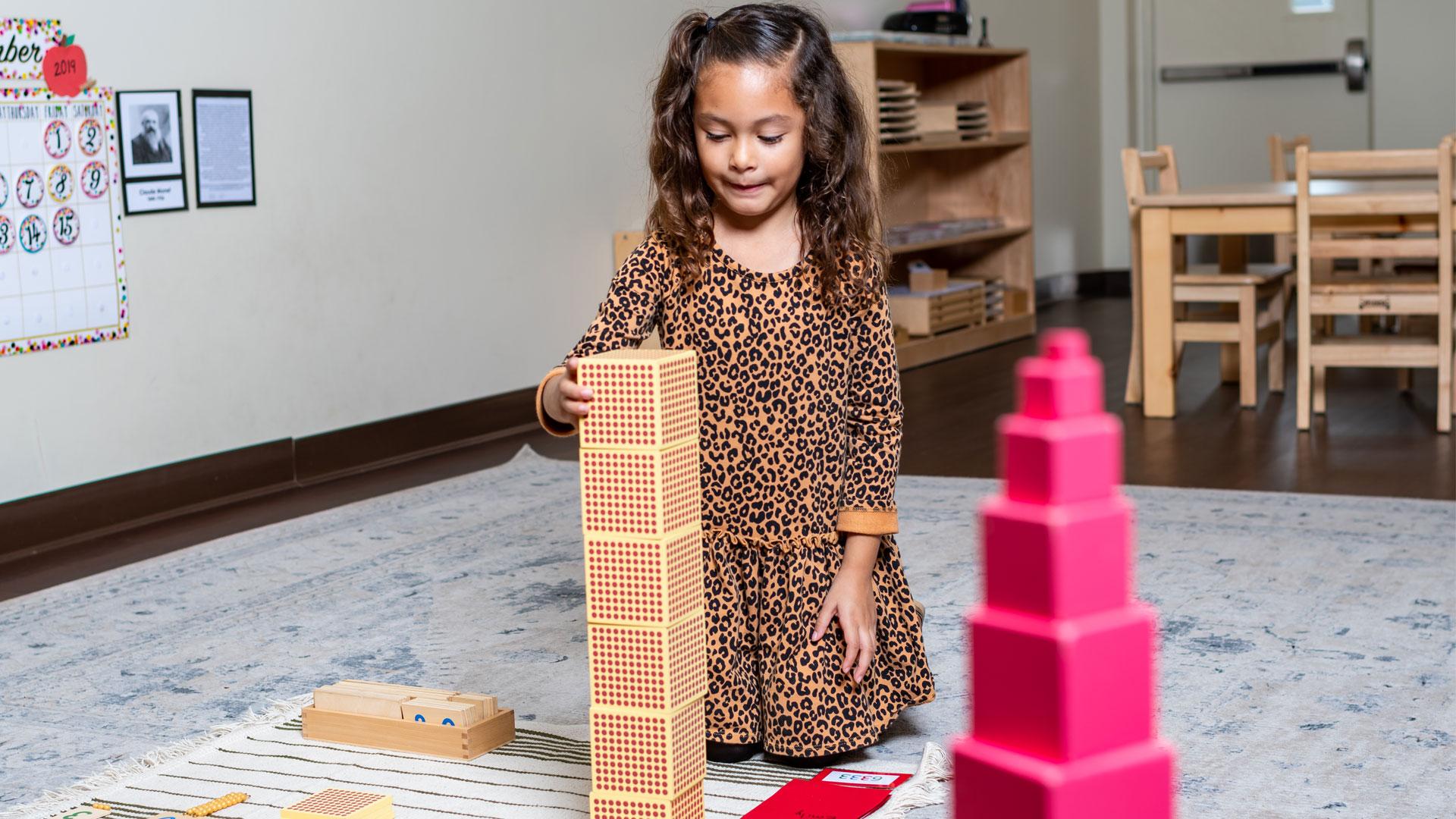 A little girl playing wooden blocks