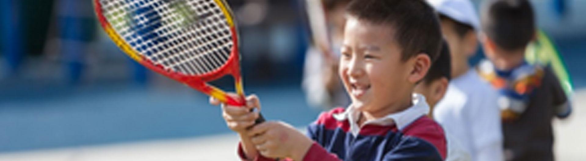 An Asian boy holding a tennis racket