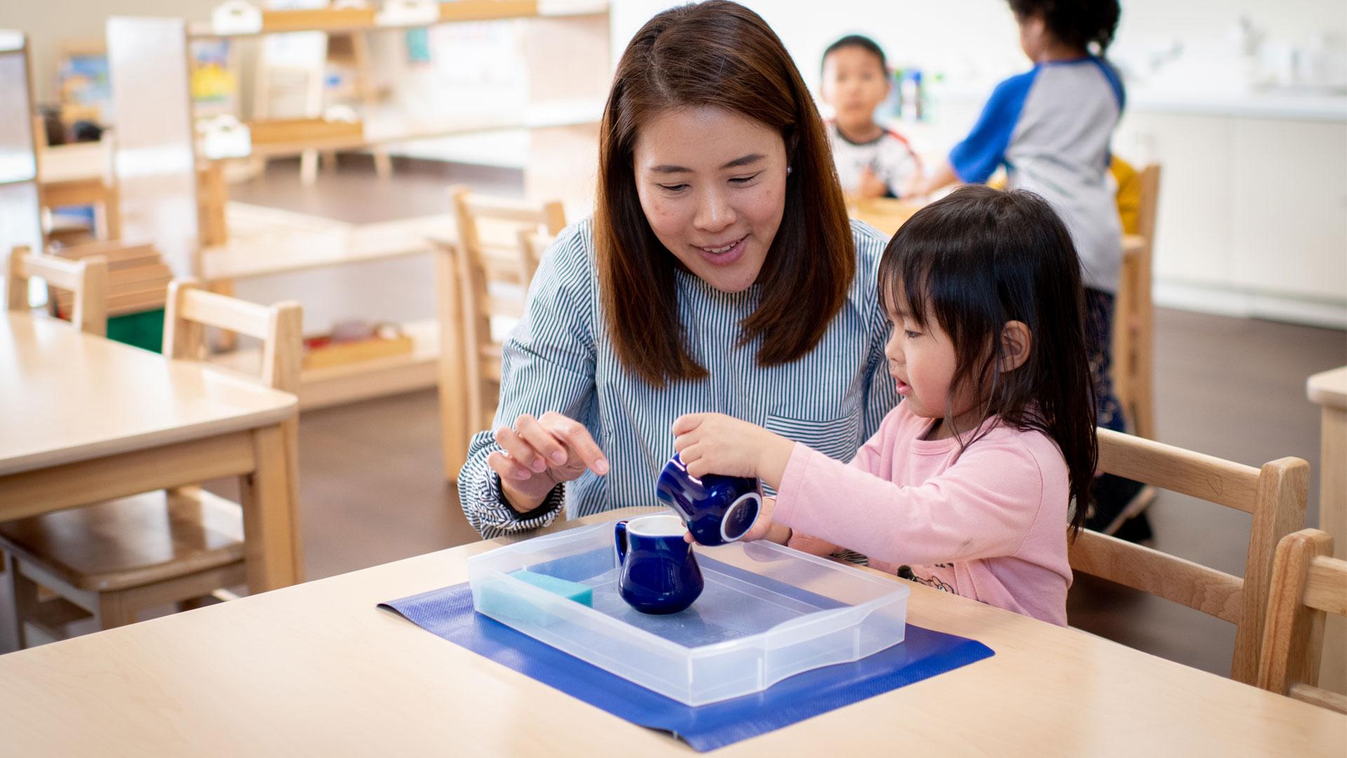 A teacher guiding a little girl