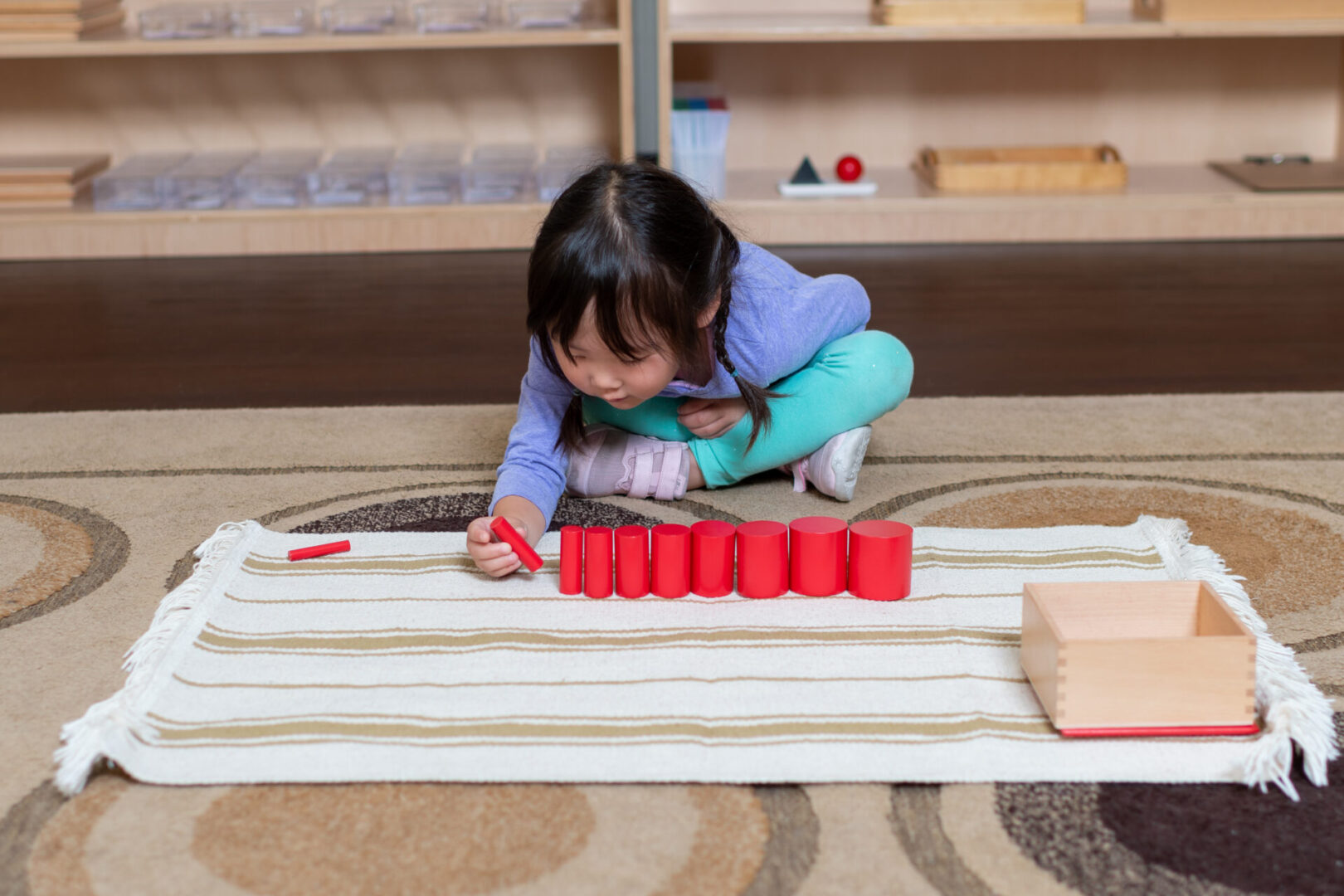 A cute little girl playing with wooden blocks