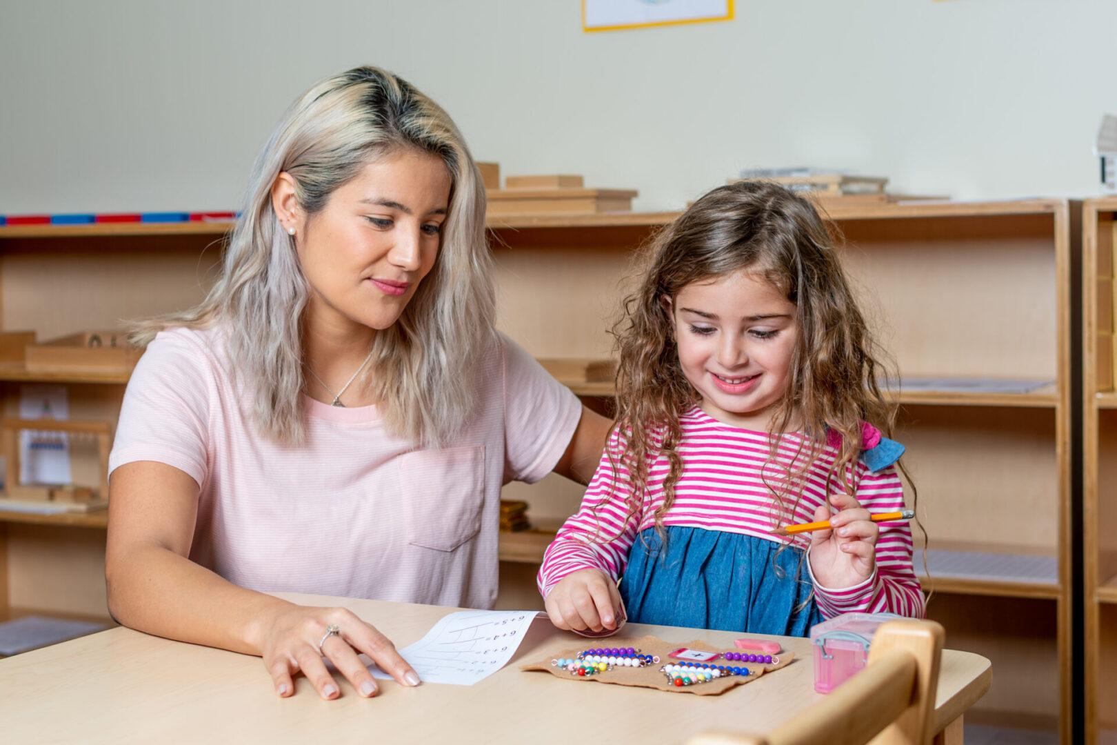 A teacher beside a little girl